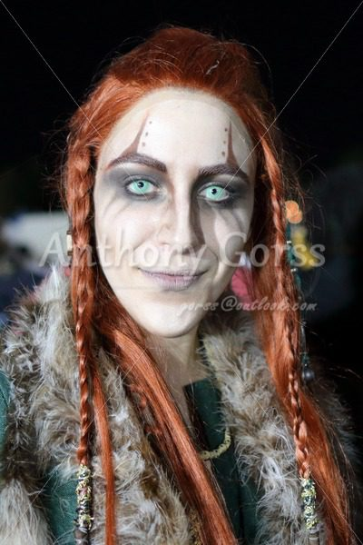 Woman with long braided orange hair and altered pupils